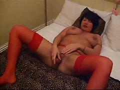 In red, in bed and masturbating