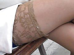 Touching her stockings top on a bus stop