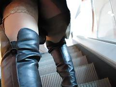 Girl in black leather boots and tan stockings on escalator