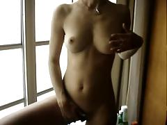 Cybel in bikini stripping in front of the window